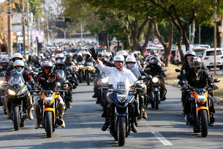 Em uma avenida de Goiânia, o presidente Jair Bolsonaro e apoiadores dirigem motocicletas