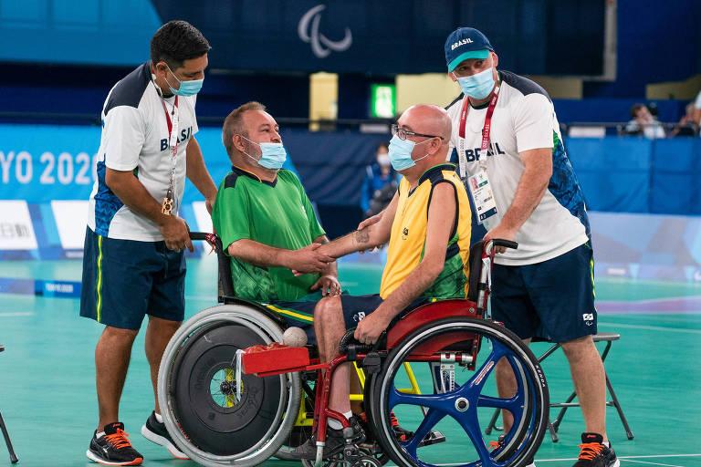 Duas pessoas em cadeiras de rodas, conduzidas por ajudantes, se cumprimentam