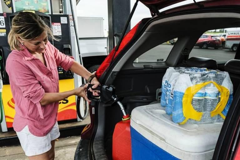 Mulher compra combustível extra e mantimentos após autoridades dizerem para cidadãos buscarem abrigo