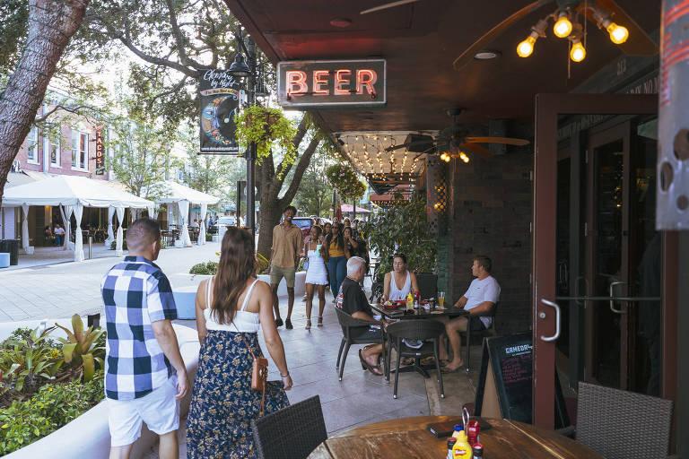 """Pessoas aparecem caminhando em uma calçada. À direita da foto, há mesas em frente a um restaurante. Em uma delas, há três pessoas sentadas. Há um letreiro escrito """"Beer""""."""