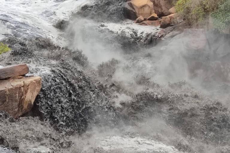 Imagem mostra trecho do rio Tietê em Salto, no interior de SP, com tonalidade escura da água