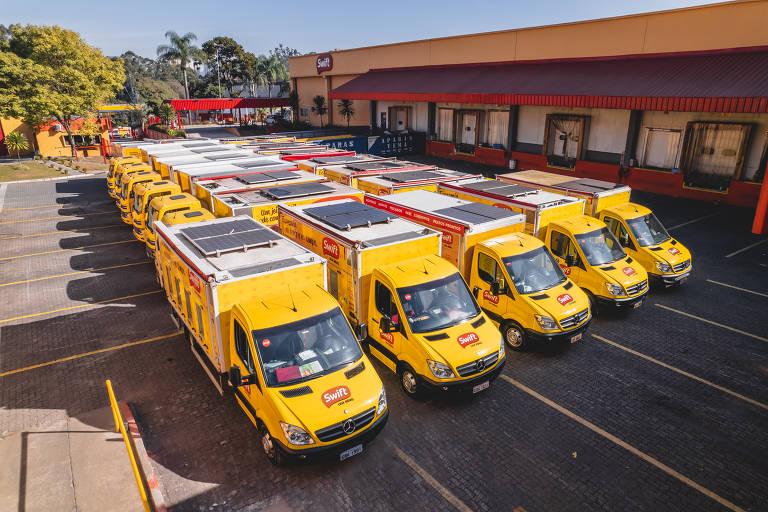 Vans amarelas aparecem em um estacionamento. Elas têm placas solares instaladas na parte superior.
