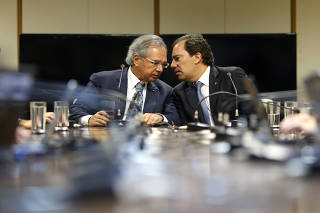 Brazil's Economy Minister Paulo Guedes talks with Caixa Economica Federal Bank President Pedro Guimaraes during a news conference in Brasilia