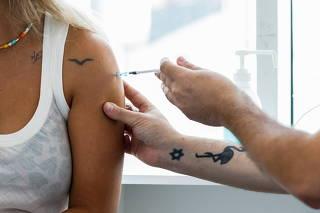 An Israeli woman receives a third shot of coronavirus disease (COVID-19) vaccine in Tel Aviv