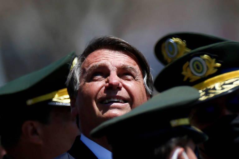 O presidente Jair Bolsonaro em meio a militares; na foto se vê apenas o rosto de bolsonaro e quepes de militares