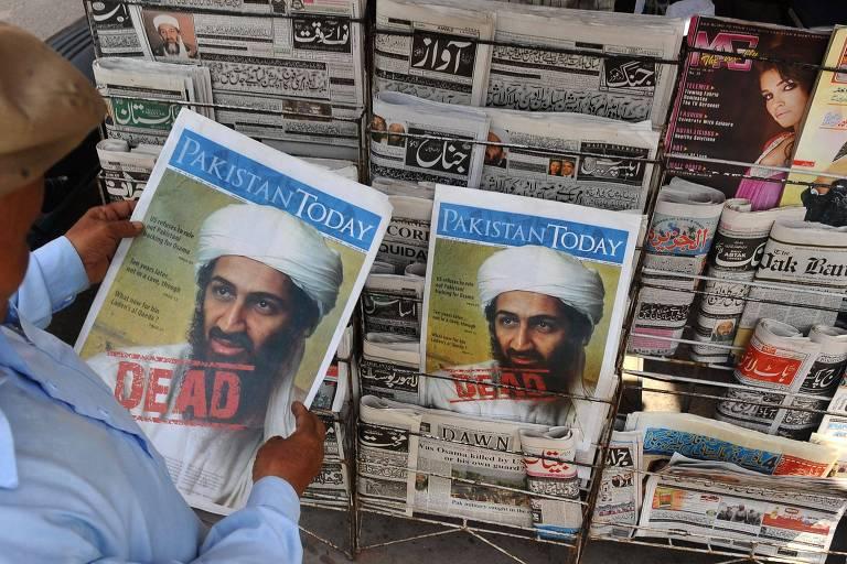 Um paquistanês lê um jornal com a primeira página exibindo a notícia da morte de Osama bin Laden em uma banca, em Lahore, no Paquistão