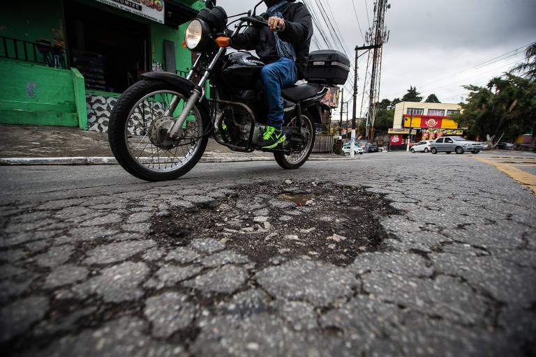 buraco em asfalto com motociclista ao lado