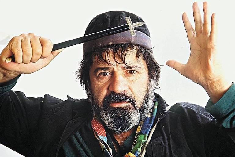 homem de cabelos embaraçados, grisalhos, usa boné posa para foto olhando fixamente para frente. ele está com as duas mãos erguidas