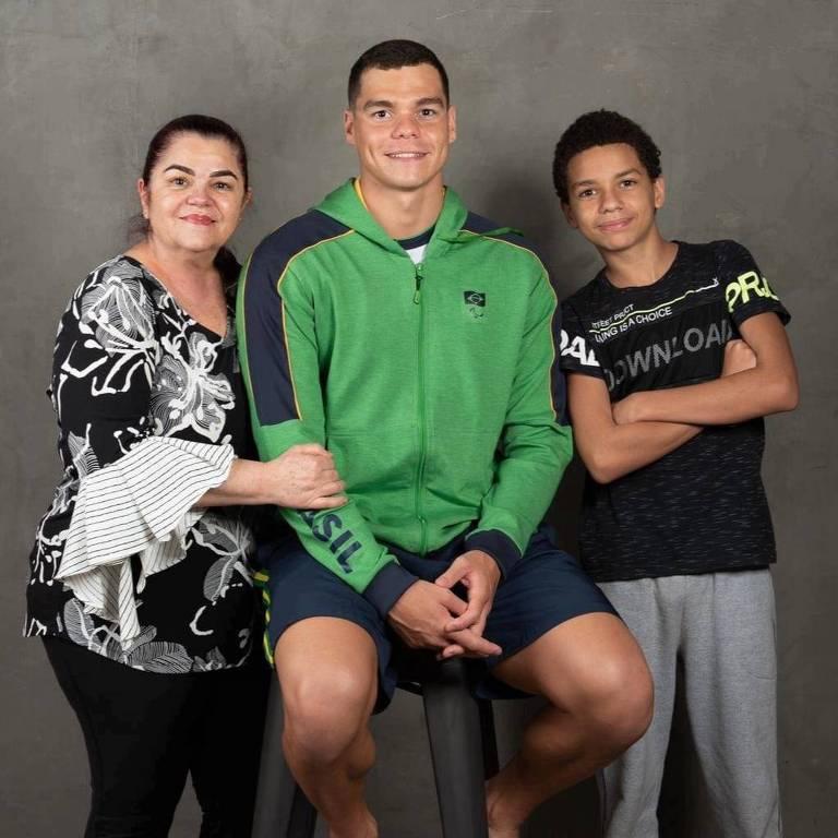 Gabriel Bandeira de casaco verde sentado entre a avó e o irmão, que estão de pé
