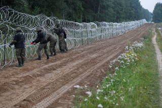 Polish soldiers build a fence on the border between Poland and Belarus near the village of Nomiki