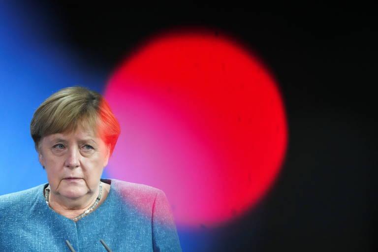 De blusa azul turqueza, Merkel olha para sua esquerda, onde está uma grande bola de luz vermelha