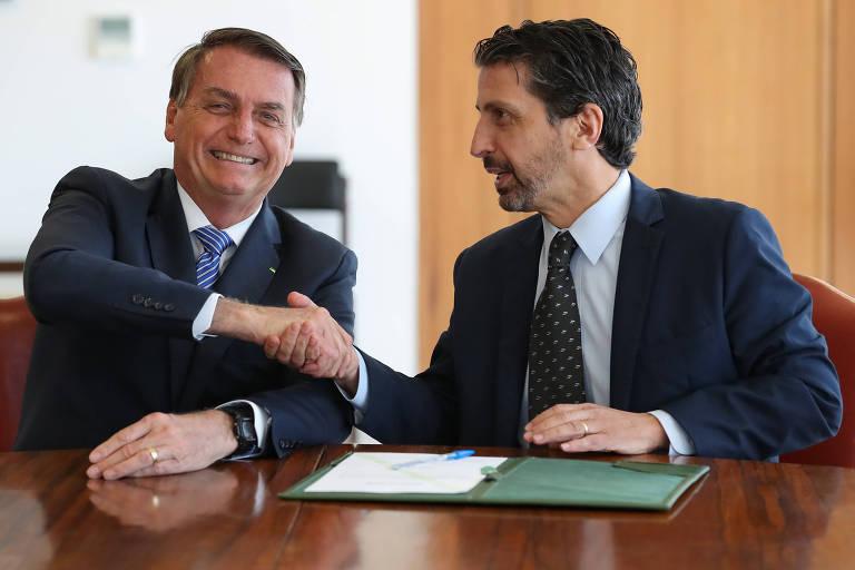 Bolsonaro ri e aperta a mão do ministro, os dois sentados em  frente a uma mesa onde há uma pasta verde com um papel em cima