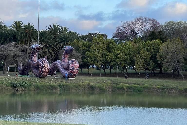 Obra em parque, na frente de lagoa, de duas serpentes coloridas e de grandes dimensões