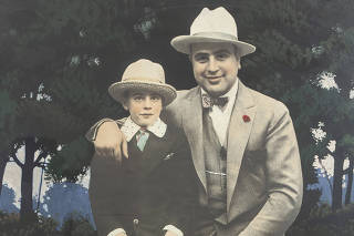 An image provided by Witherell's shows a hand-colored photograph of Al Capone at age 27 with his son in Hot Springs, Ark., circa 1925. It is one of many items related to the mobster that are going up for auction. (Witherell's via The New York Times)
