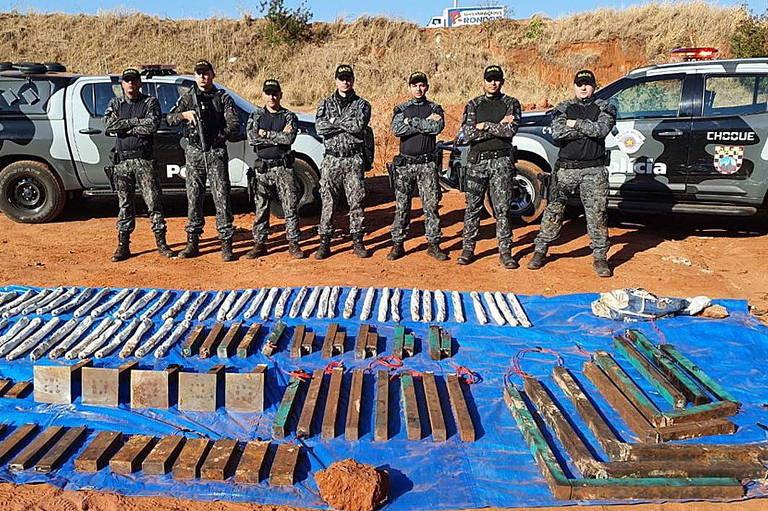 Dezenas de explosivos e bananas de emulsão estão sob um toldo azul no chão. Ao fundo, sete agentes da polícia posam em pé, com os braços cruzados. Atrás deles, dois carros da polícia estão parados.