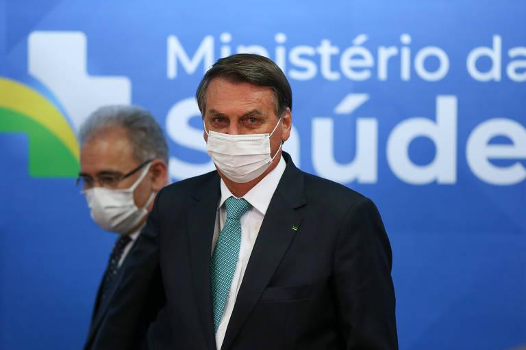 """Presidente Jair Bolsonaro em primeiro planto. Marcelo Queiroga, ministro da Saúde, em segundo plano. Ambos aparecem à frente de um banner azul onde se lê """"Ministério da Saúde""""."""