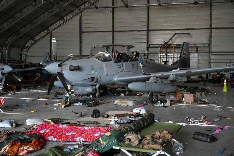 Dois Super Tucano em hangar com coletes à prova de bala espalhados no chão