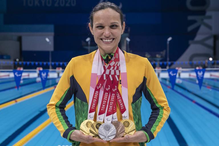 Carol em frente à piscina com cinco medalhas penduradas no pescoço