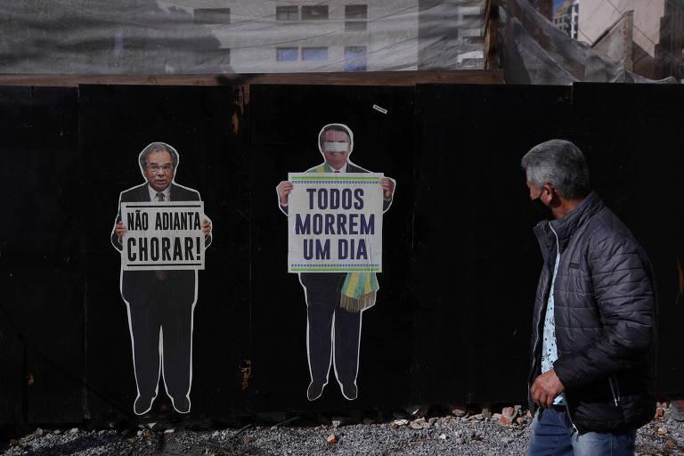 Homem passa por rua com cartazes criticando o ministro Paulo Guedes, da Economia, e o presidente Jair Bolsonaro