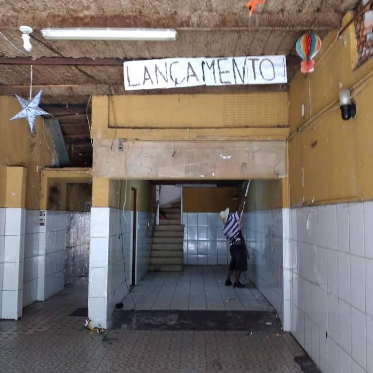 Homem em um ambiente com uma placa escrita 'lançamento', pintando a parede de amarelo