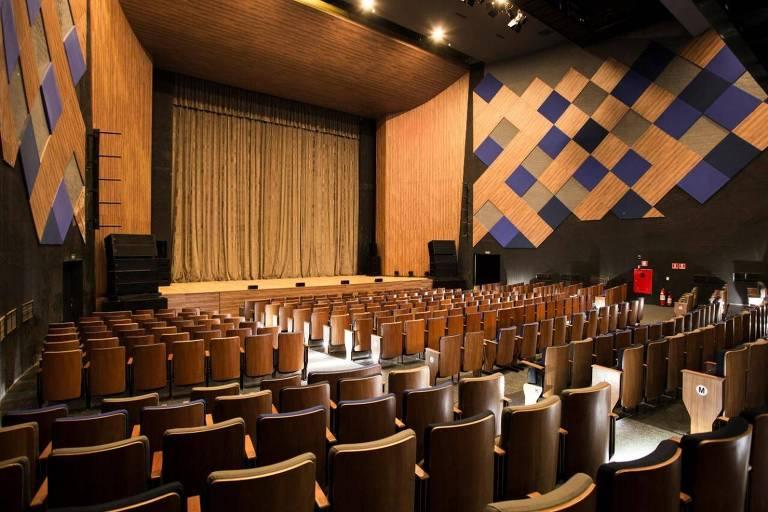 A imagem mostra a plateia de um teatro, vazia e o palco com as cortinas fechadas
