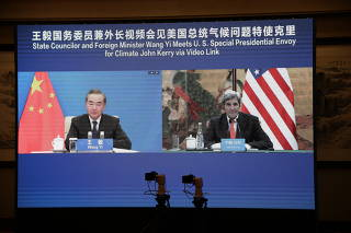 John Kerry is seen on a screen with Wang Yi during a meeting via video link
