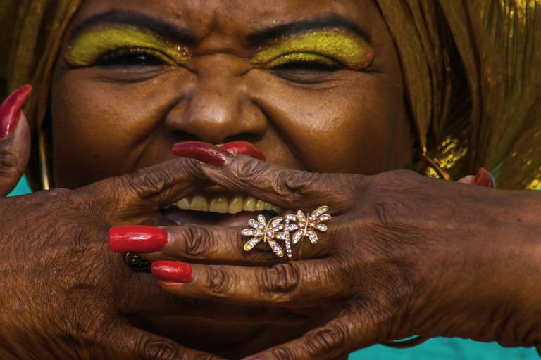 Uma mulher negra está com as mãos no rosto deixando uma pequena abertura entre os dedos por onde dá para ver seus dentes. Ela sorri com os olhos e usa maquiagem amarela