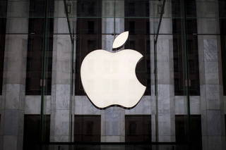 FILE PHOTO: An Apple logo hangs above the entrance to the Apple store on 5th Avenue in the Manhattan borough of New York City