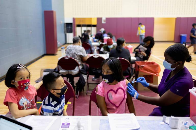 Foto mostra grupo de três crianças, com máscaras, sentadas a uma mesa, num ambiente colorido; a que está mais à direita é Victoria Zaca, 12, e recebe a injeção de uma profissional de saúde negra, com máscara e luvas