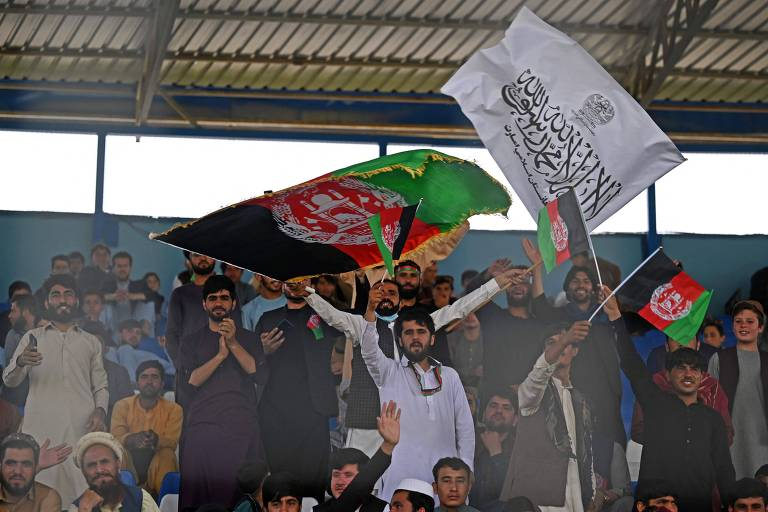Torcedores agitam bandeira do Afeganistão e do Talibã (branca) em jogo no Estádio Internacional de Críquete de Cabul