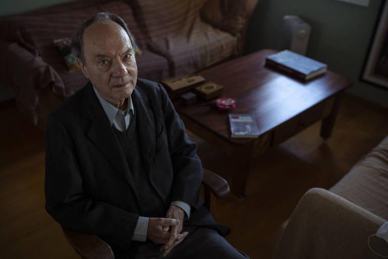Homem sentado em cadeira ao lado de mesa e sofás