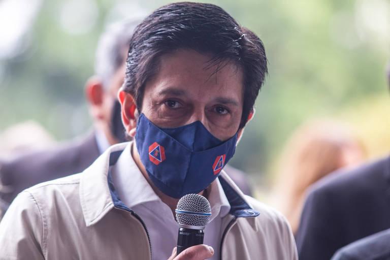 Prefeito Ricardo Nunes de máscara azul e falando ao microfone