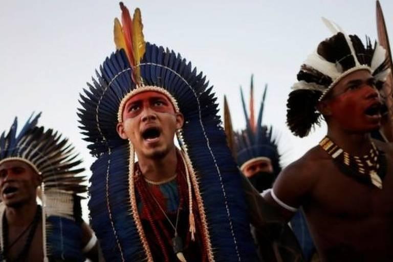 Imagem mostra homens indígenas com cocar