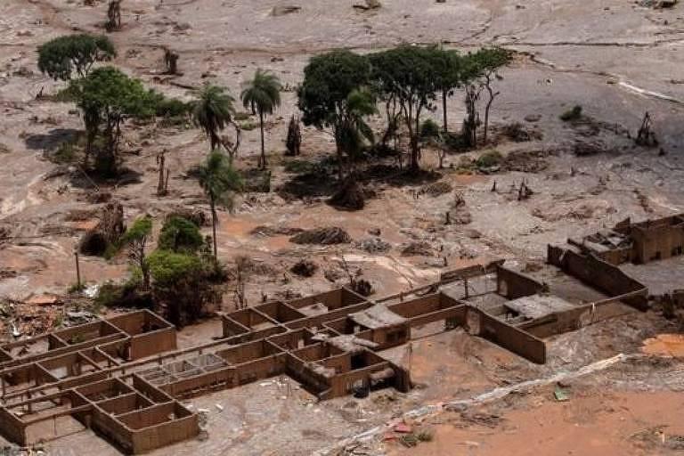 Imagem aérea mostra área rural tomada pela lama após rompimento de uma barragem