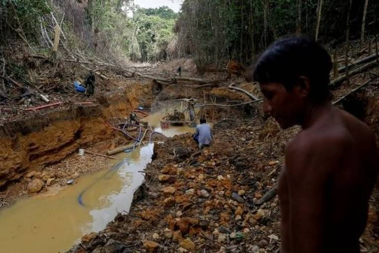 Homens estão a beira de um rio cercado por vegetação onde há extratão de minério