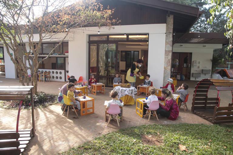 Crianças fazem atividade na área externa da escola, mesas pequenas e coloridas estão dispostas no jardim
