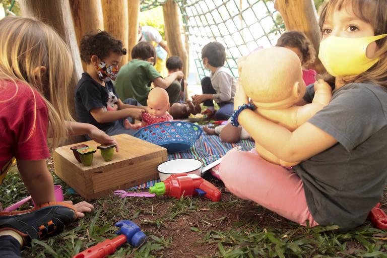 Crianças pequenas, sentadas em círculo seguram brinquedos em área externa na escola
