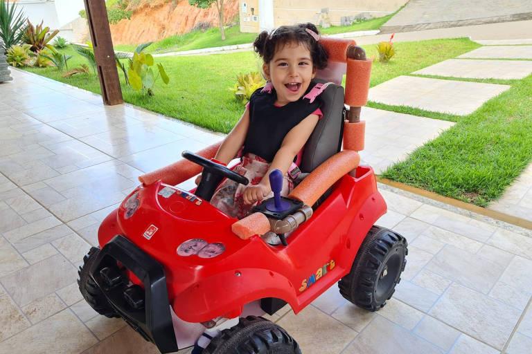 Criança sorrindo, sentada em seu carrinho vermelho, adaptado pelo projeto Adapt