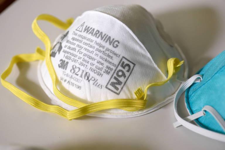 "Máscara branca com elásticos amarelos sobre mesa branca; nela está escrito, em cinza, ""N95"" e avisos; à direita dela, cortada na foto, uma máscara azul"