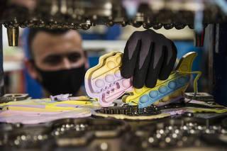 Fabrica Luka Plasticos  de pop-its no interior de S‹o Paulo vende 200 mil unidades em 50 dias: Funcionario Paulo Henrique,18, retira dos moldes em aco da prensa vulcanizada, pecas de silicones coloridos  de  pop-its, um dos fidget toys da moda (os brinquedos para desestressar), explodiu no Brasil a partir dos influenciadores do YouTube e do TikTok.