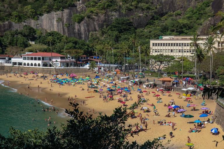 Vista aérea da praia da Urca; nna faixa de areia há pessoas em dia de sol