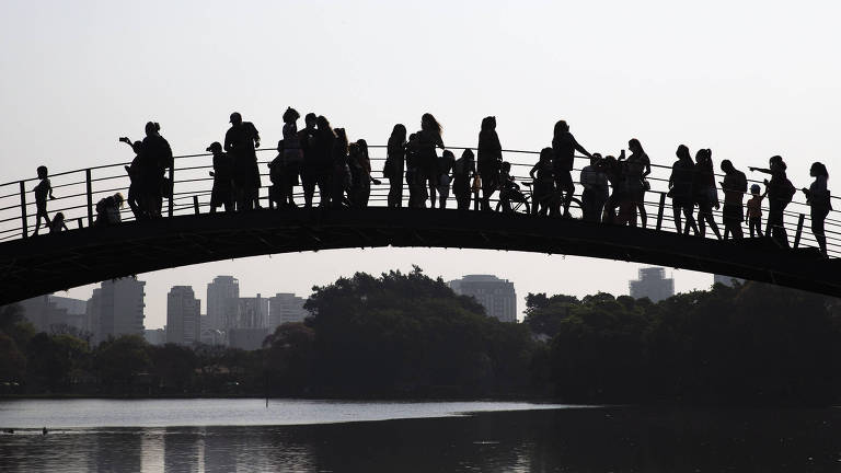 Silhueta das pessoas em cima da passarela do Parque Ibirapuera é vista ao longe, em cima do lago