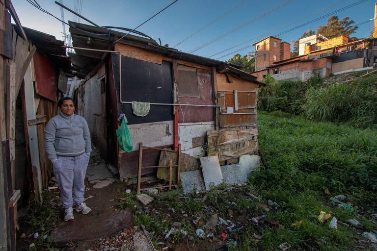 Fernanda Cristina na frente de sua casa, ao lado do esgoto a céu aberto na favela do Pullman, em São Paulo