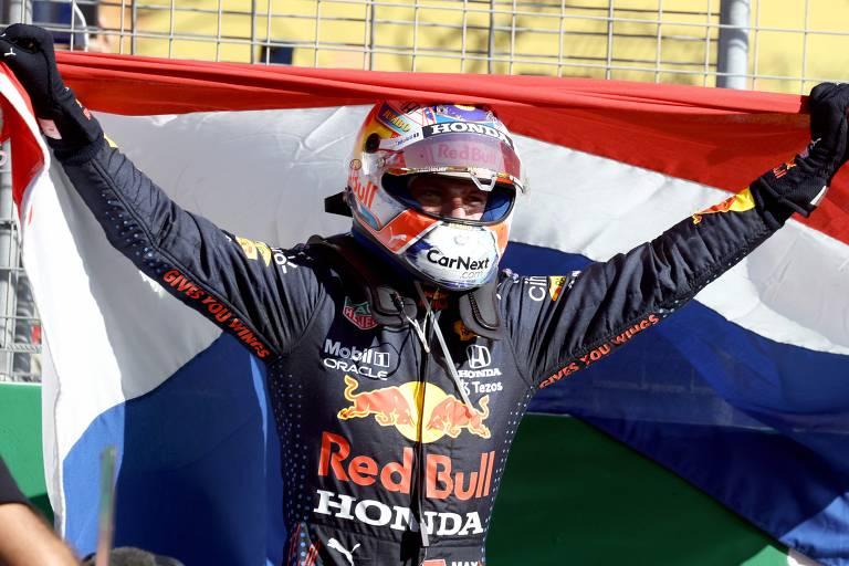 O holandês Max Verstappen comemora a vitória, no GP da Holanda, com uma bandeira do seu país