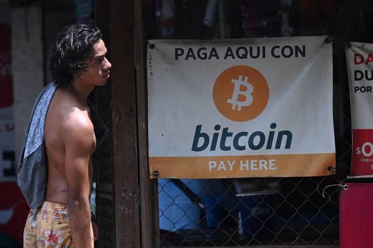 """homem em frente a pequena loja com cartaz em espanhol em que se lê """"aceitamos bitcoin"""""""