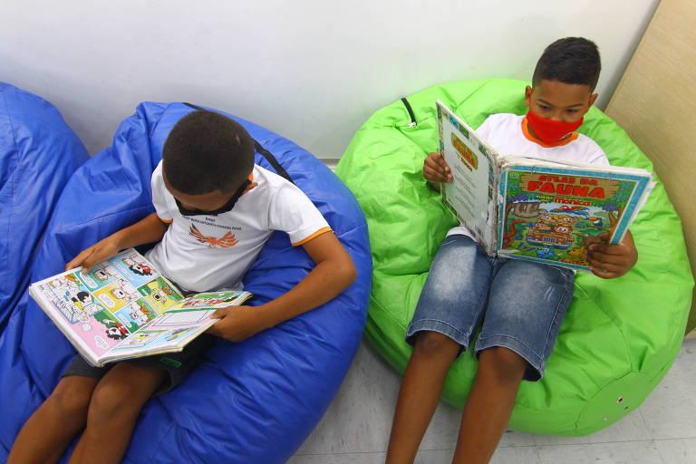 Dois meninos aparecem sentados lendo livros.