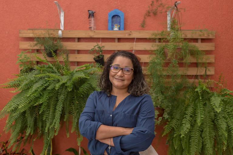 Mulher vestindo camisa azul com os braços cruzados em frente a um estrado de cama adaptado para um jardim vertical, pendurado em uma parede salmão