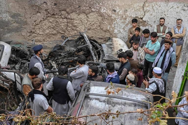 Moradores e parentes de vítimas de ataque americano com drone próximo a carro destruído em Cabul, no Afeganistão