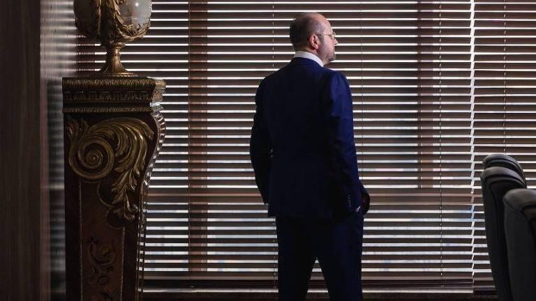 Homem de terno azul, virado de costas em frente a uma janela