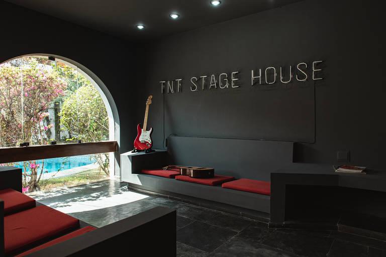 Ambiente da TNT Stage House; paredes são pretas, há sofá co assento vermelho e uma passagem pela qual se vê a piscina do lado de fora